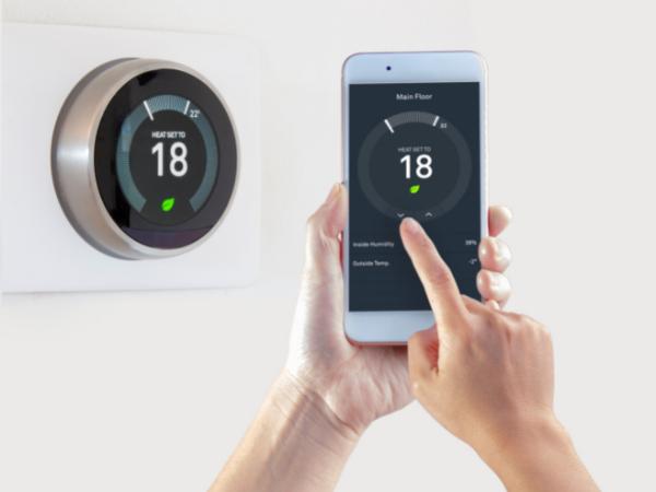 person adjusting smart thermostat