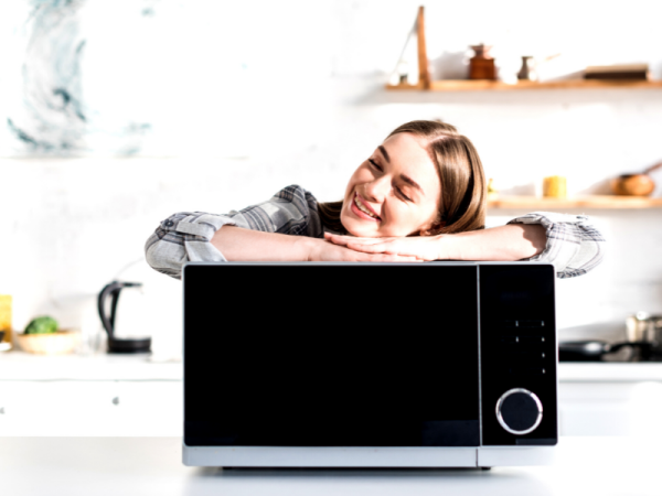 lady lying on top of microwave