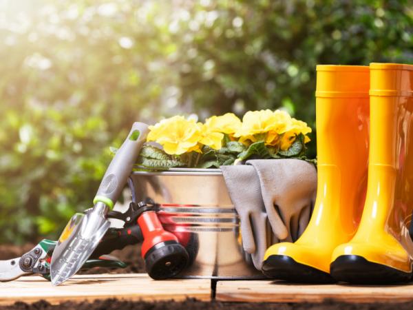 yellow gardening boots next to garden tools